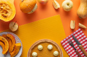 delicious pumpkin pie with whipped cream near baked and raw pumpkins, whole and cut apples, fork and knife on orange surface
