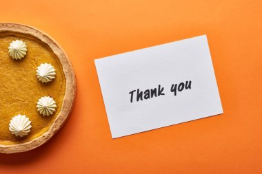 Top view of pumpkin pie and thank you card on orange background stock vector
