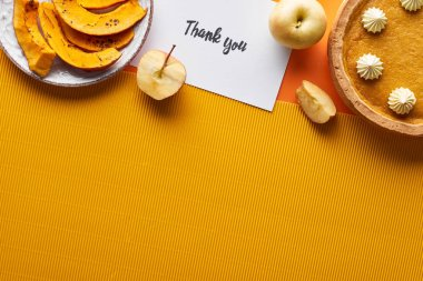 top view of pumpkin pie, ripe apples and thank you card on orange background with copy space