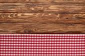 vista superiore di tovagliolo rosso a scacchi su tavolo marrone in legno