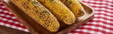 grilled corn served on red checkered napkin at wooden table for Thanksgiving dinner, panoramic shot
