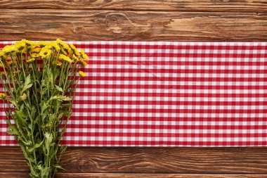 Top view of yellow wildflowers on red checkered napkin at wooden table stock vector