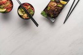 top view of delicious spicy thai noodles with chopsticks on marble grey surface