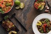 Fotografie top view of fresh spicy thai noodles with chopsticks on stone surface