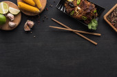 Fotografie top view of tasty spicy thai noodles near chopsticks and fresh ingredients on wooden grey surface with copy space