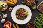 vrchní pohled na chutné pikantní masové thajské nudle v blízkosti hůlek a čerstvých ingrediencí na dřevěném šedém povrchu