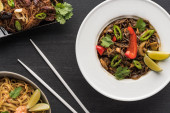 Fotografia top view of tasty spicy thai noodles near chopsticks on wooden grey surface