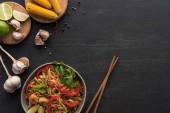 top view ízletes fűszeres thai tészta garnélarák közelében evőpálcikák és friss összetevők fa szürke felületen másolás hely
