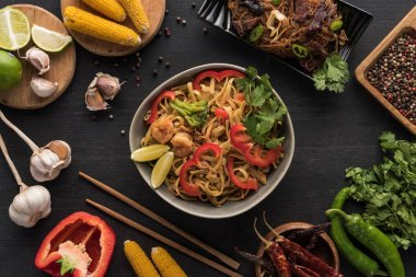 top view of tasty spicy seafood thai noodles near chopsticks and fresh ingredients on wooden grey surface