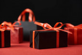selective focus of presents with red ribbons and shopping bag isolated on black