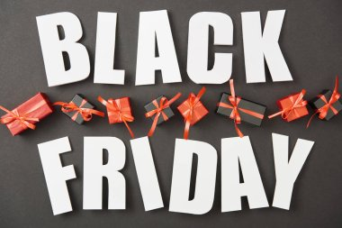 Top view of black friday white lettering near presents on black background stock vector