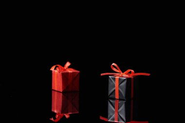 Selective focus of black and red decorative gifts isolated on black stock vector