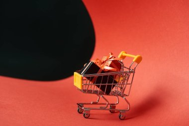 Decorative gifts in small shopping cart on red paper isolated on black stock vector