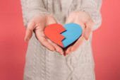 cropped view of woman holding paper red and blue broken heart on pink