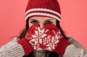 žena v pleteném klobouku zakrývající tvář s červenými a teplými rukavicemi izolovanými na růžové