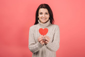 happy woman in warm sweater holding paper cut with broken heart on pink