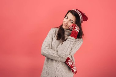 Cheerful woman in red knitted hat and gloves looking at camera on pink stock vector
