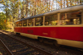 motion blur of tram with passengers on railway in autumnal forest with golden foliage in sunlight