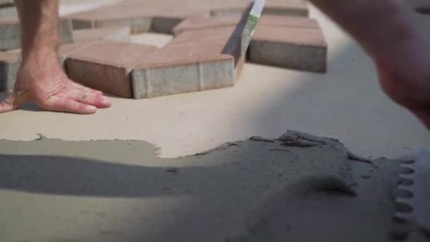 worker applies glue to tiles on pavement.
