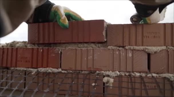 Pracovník v těsné blízkosti industriální zednář instaluje cihlové a třecí cihly na staveništi. Pracovník vytváří dům barevných cihel.