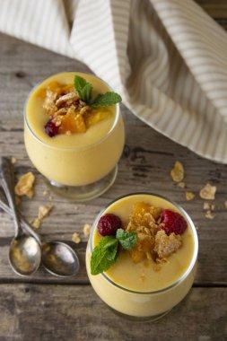 Mango milkshake or smoothie in a glass on the old wooden background. Mango milk shake. Summer refreshing drink concept.