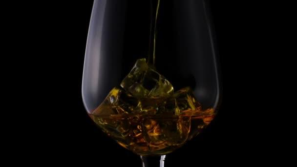 Whisky ömlött egy üveg, jégkocka, ban lassú mozgás, Vértes lövés, a fekete háttér. Koncepció: alkohol, szesz, jó estét, jó éjszakát, alkohol károsítja egészségét.