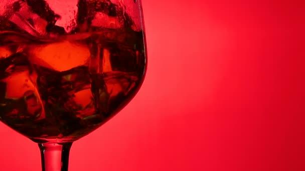 Whisky ömlött egy üveg, jégkocka, ban lassú mozgás, Vértes lövés, piros háttéren. Koncepció: alkohol, szesz, jó estét, jó éjszakát, alkohol károsítja egészségét.