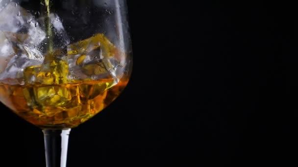 Whisky ömlött egy üveg, jégkocka, ban lassú mozgás, Vértes lövés, sötét háttér előtt. Koncepció: alkohol, szesz, jó estét, jó éjszakát, alkohol károsítja egészségét.