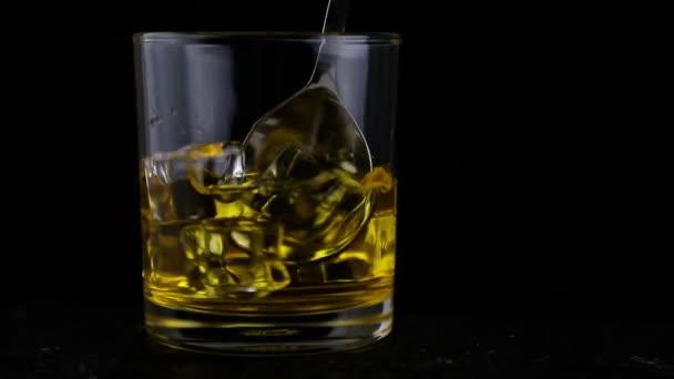 Jégkockák, lassú mozgás, közelkép, lövés, a fekete háttér egy pohár whisky. Koncepció: alkohol, szesz, jó estét, jó éjszakát, alkohol károsítja egészségét.