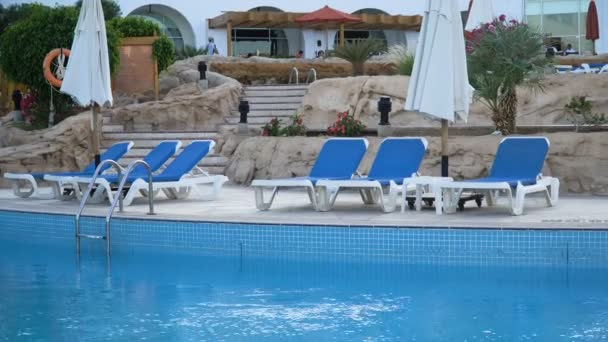 Stunning empty hotel beach with fancy white daybeds, loungers and sunshades in expensive luxurious resort on sunny summer day