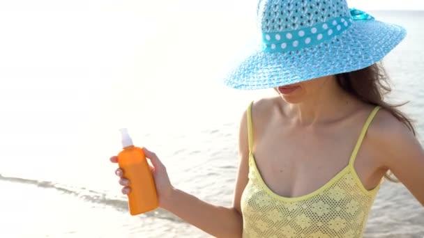 Opalovací krém žena použití opalovací krém na ramenou během cestování prázdniny. Krásná šťastná žena s opalovací olej Smetana v plastová láhev s rozprašovačem na pláži
