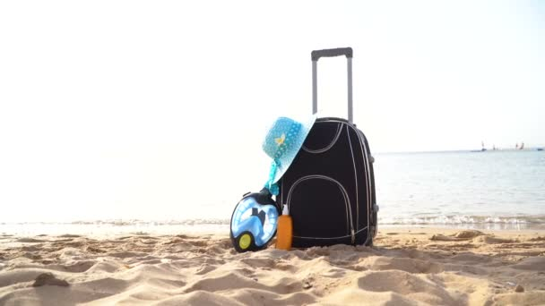 Travel holiday vacation suitcase with sunglasses, starfish, straw hat and beach slippers on the beautiful beach with palm trees. Advertisement on travel suitcase