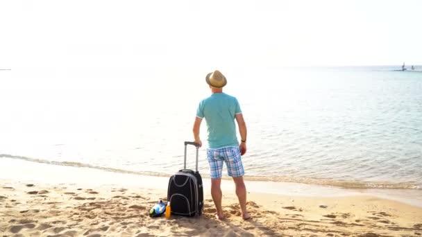 Muž s kufrem na pláži. Letní cestování a dovolené koncept