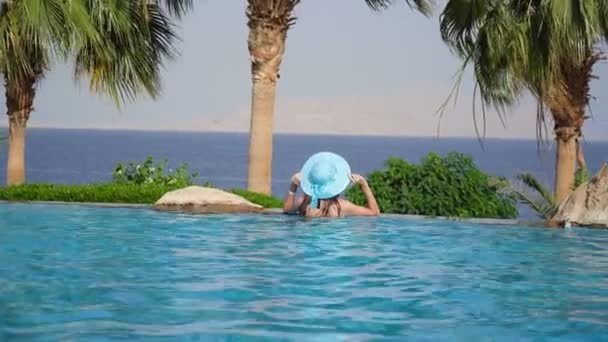 Luxury Resort. Woman Relaxing In Infinity Swimming Pool Water. Beautiful Happy Healthy Female Model Enjoying Summer Travel Vacation, Looking At Sea View. Summertime Recreation, Relax And Spa Concept