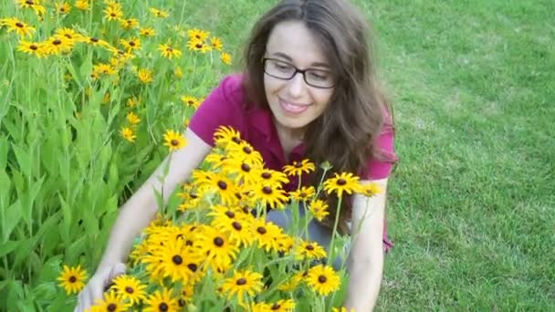 Outdoor portrait of young beautiful fashionable woman smells yellow flowers