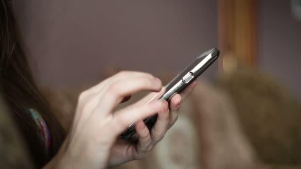 Krásná mladá žena pomocí telefonu sedí na gauči doma. Žena procházení webu, sociální sítě, hledá něco v internetovém obchodě. Vnitřní