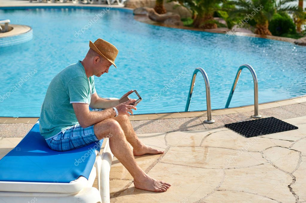 Man using mobile phone on vacation by the pool in hotel, concept of a freelancer working for himself on vacation and travel