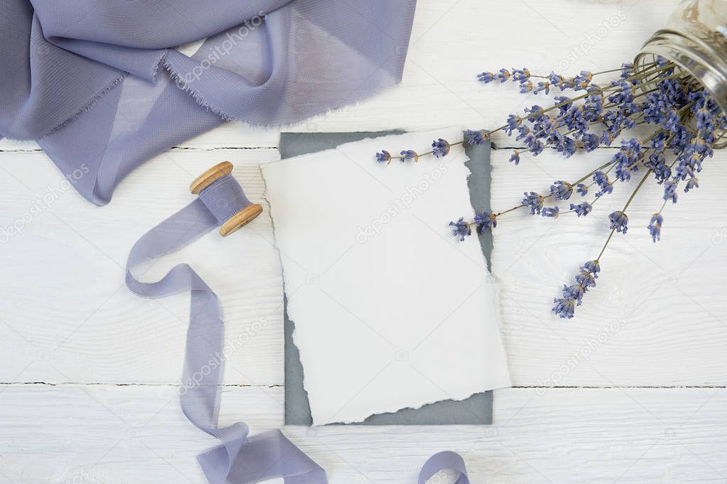 White blank card on a background of blue ribbon with lavender flowers on a white background. Mockup with envelope and blank card. Flat lay. Top view
