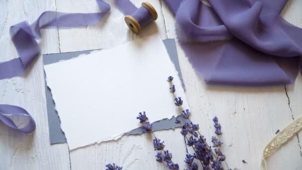 Bílé prázdné vizitky, obálky a stuha na pozadí růžové a modré látky s levandulovými květy na bílém pozadí. Maketa s obálkou a prázdnou kartu. Byt leží. Pohled shora