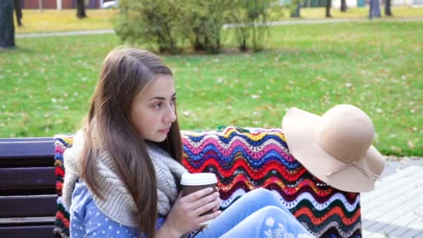 Woman Relaxes on the Bench in Beautiful Green Park with cup of coffee. 4K video motion. attractive girl sits on a wooden bench among greens. Female sitting on a bench in a picturesque place