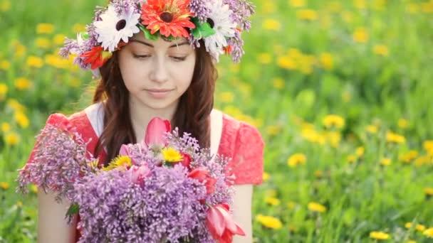 Nő a koszorút a fejét csákány lila és a tulipán virágok kertben. Boldog nő Kertész virágokkal. Tavasz és nyár. Szeretek dolgozni növények