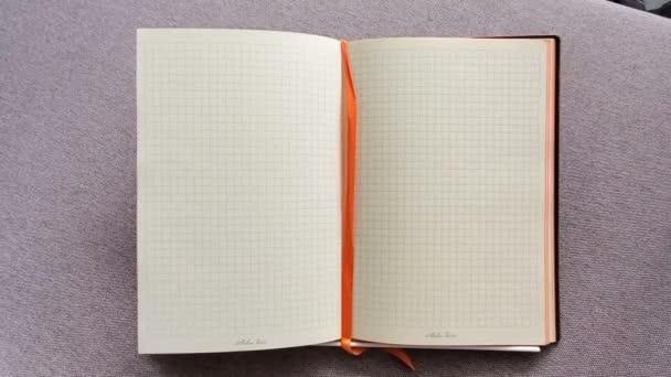 Otevřete Poznámkový blok v kleci na stole. Otevřete deník v krabici. Pohyb videa zblízka. Obchodní koncepce, místo pro text. Kopírování místa pro text