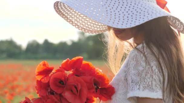 Uprostřed pole máku stojí mladá brunetka v bílých šatech a s velkým kloboukem. Okouzlující dáma s neuvěřitelným úsměvem s kyticí máku v rukou. Zpomalení plného HD