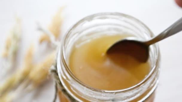 Med stéká ze lžíce do sklenice