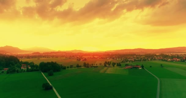 Amazing aerial sunset view of green european fields, golden sky, twilight on Bavarian Alps, Bavaria, Germany.