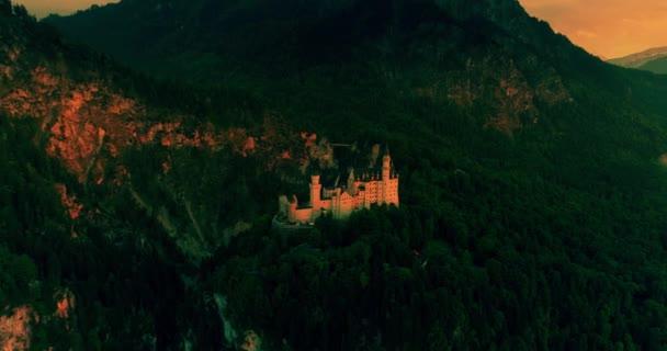 Erstaunlichen Sonnenuntergang Luftaufnahme von Schloss Neuschwanstein, goldenen Himmel, Twilight auf die Bayerischen Alpen, Bayern, Deutschland.