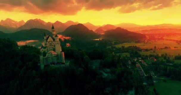atemberaubende Luftaufnahme des Sonnenuntergangs von Schloss Neuschwanstein, goldener Himmel, Dämmerung auf den bayerischen Alpen, Bayern, Deutschland 4k