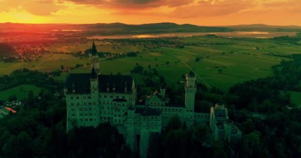 Incredibile vista tramonto aerea del Castello di Neuschwanstein, cielo dorato, crepuscolo sulle Alpi bavaresi, Baviera, Germania