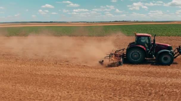 Légi drone megtekintése a búza területen dolgozó piros tracor. Mezőgazdaság és környezetvédelem az Európai Unióban.