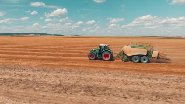 Letecký pohled na letící nad pšeničné pole a spojit kombajn traktor s přívěsem, který dělá hromádky pšenice na léta den 4k.